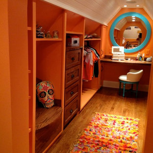 Design ideas for a mid-sized eclectic gender-neutral dressing room in New York with shaker cabinets and medium wood cabinets.