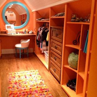 Diseño de vestidor unisex, ecléctico, de tamaño medio, con armarios estilo shaker, puertas de armario de madera oscura y suelo de madera en tonos medios