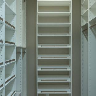 Réalisation d'un dressing tradition de taille moyenne et neutre avec un placard sans porte, des portes de placard blanches, un sol en bois foncé et un sol marron.