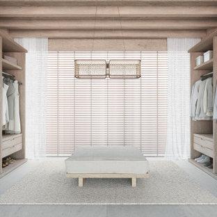 Inspiration för moderna garderober, med öppna hyllor, skåp i ljust trä, kalkstensgolv och beiget golv