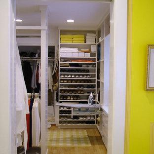 Immagine di una grande cabina armadio unisex design con nessun'anta e ante bianche