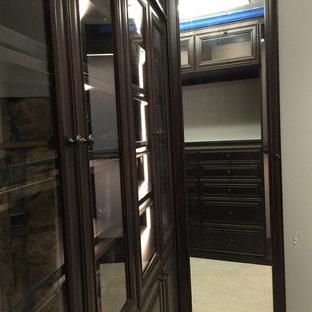 Foto di una cabina armadio unisex tradizionale con ante a filo, ante in legno bruno e pavimento in legno verniciato