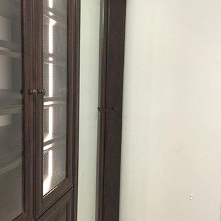 Idee per una cabina armadio unisex classica con ante a filo, ante in legno bruno e pavimento in legno verniciato