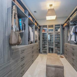Modelo de vestidor unisex, actual, grande, con armarios con paneles lisos, moqueta, suelo beige y puertas de armario grises