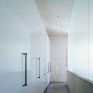 Cette image montre un dressing design neutre avec un placard à porte plane, des portes de placard blanches et un sol en ardoise.
