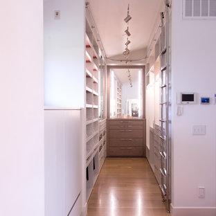 Modelo de armario vestidor unisex, actual, de tamaño medio, con armarios con paneles lisos, puertas de armario blancas, suelo de madera clara y suelo beige