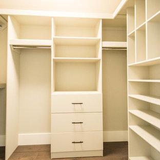 Diseño de armario vestidor unisex, clásico, de tamaño medio, con armarios abiertos, puertas de armario rojas, suelo de madera en tonos medios y suelo marrón