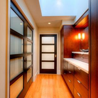 Imagen de vestidor de hombre, minimalista, de tamaño medio, con armarios con paneles lisos, puertas de armario de madera en tonos medios, suelo de madera en tonos medios y suelo marrón
