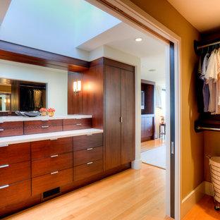 Mittelgroßes Modernes Ankleidezimmer mit flächenbündigen Schrankfronten, braunen Schränken, braunem Holzboden, braunem Boden und Ankleidebereich in Seattle