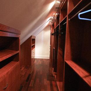 Immagine di una grande cabina armadio unisex classica con ante in legno scuro e pavimento in legno massello medio