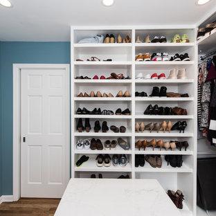 Diseño de armario vestidor de hombre, romántico, grande, con armarios con paneles lisos, puertas de armario blancas, suelo de madera en tonos medios y suelo marrón