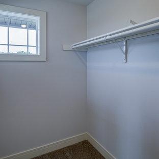 Immagine di un'ampia cabina armadio unisex contemporanea con moquette e pavimento marrone