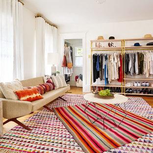 Exemple d'un grand dressing room éclectique avec un sol en bois brun et un placard sans porte.