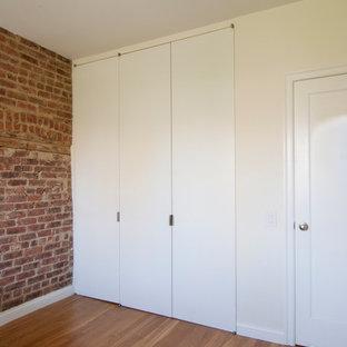 Foto de armario unisex, urbano, de tamaño medio, con armarios con paneles lisos, puertas de armario blancas, suelo de madera en tonos medios y suelo marrón