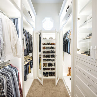 Inredning av ett klassiskt stort walk-in-closet för könsneutrala, med vita skåp, heltäckningsmatta, luckor med infälld panel och brunt golv