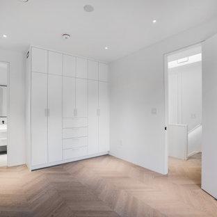 Modelo de armario y vestidor unisex, tradicional renovado, de tamaño medio, con armarios con paneles lisos, puertas de armario blancas, suelo de madera clara y suelo blanco