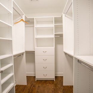 Photo of a mid-sized transitional gender-neutral walk-in wardrobe in Philadelphia with white cabinets, medium hardwood floors and flat-panel cabinets.