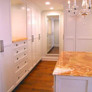 Imagen de armario vestidor unisex, clásico, grande, con armarios estilo shaker, puertas de armario blancas, suelo de madera en tonos medios y suelo marrón