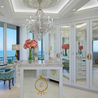 Idée de décoration pour un dressing room victorien avec un placard avec porte à panneau encastré, des portes de placard blanches et un sol beige.