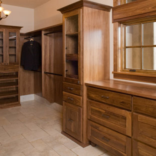 Inspiration for a large mediterranean gender neutral walk-in wardrobe in Portland with recessed-panel cabinets, dark wood cabinets and travertine flooring.
