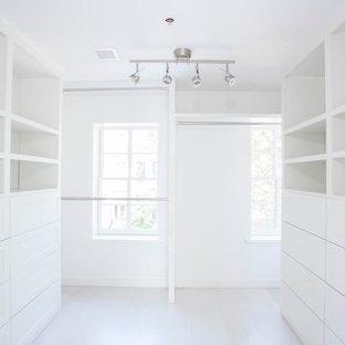Idéer för ett stort modernt omklädningsrum för könsneutrala, med luckor med infälld panel, vita skåp och målat trägolv