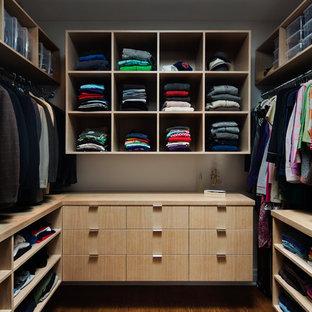 Foto de armario vestidor unisex, contemporáneo, pequeño, con armarios con paneles lisos, puertas de armario de madera clara y suelo de madera en tonos medios