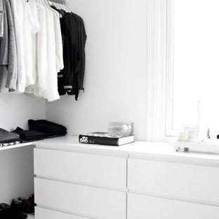Foto de armario unisex, moderno, pequeño, con armarios con paneles lisos, puertas de armario blancas y suelo blanco