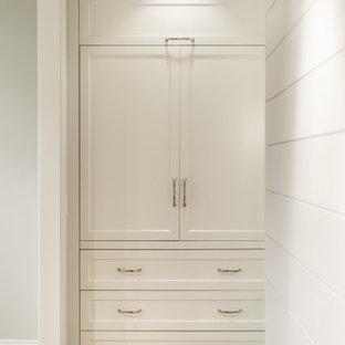 Mittelgroßes Maritimes Ankleidezimmer mit Einbauschrank, Schrankfronten im Shaker-Stil, weißen Schränken, braunem Holzboden und gewölbter Decke in Seattle