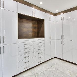 Foto de armario vestidor unisex, moderno, extra grande, con armarios con paneles lisos, puertas de armario de madera oscura y suelo de mármol