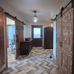 Idée de décoration pour un dressing room champêtre de taille moyenne et neutre avec un placard avec porte à panneau surélevé, des portes de placard en bois vieilli, un sol en brique et un sol multicolore.