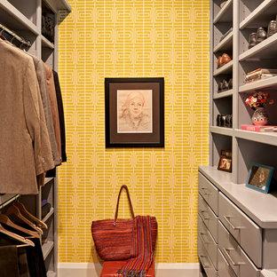 Immagine di una cabina armadio minimal con ante lisce, ante grigie, pavimento in legno massello medio e pavimento marrone