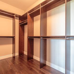 Modelo de armario vestidor unisex, de estilo americano, grande, con armarios con paneles lisos, puertas de armario marrones y suelo de madera oscura