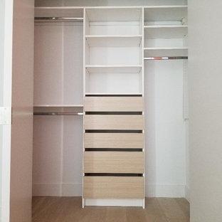 Esempio di un armadio o armadio a muro unisex minimalista di medie dimensioni con ante lisce, ante in legno chiaro, pavimento in legno massello medio e pavimento beige