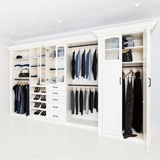 Ejemplo de armario unisex, actual, de tamaño medio, con armarios con paneles con relieve, puertas de armario blancas y suelo de baldosas de cerámica