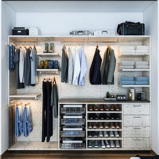 Diseño de armario pequeño con armarios con paneles lisos, puertas de armario de madera clara, suelo de madera en tonos medios y suelo marrón