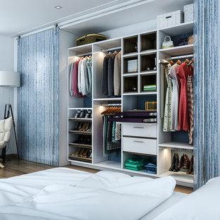 Modelo de armario pequeño con armarios con paneles lisos, puertas de armario blancas, suelo de madera en tonos medios y suelo marrón