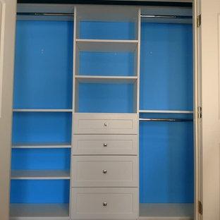 Réalisation d'un placard dressing minimaliste de taille moyenne et neutre avec un placard à porte shaker, des portes de placard blanches et un sol en bois brun.