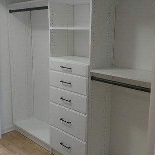 Foto de armario unisex, moderno, de tamaño medio, con armarios con paneles lisos, puertas de armario blancas y suelo de madera clara