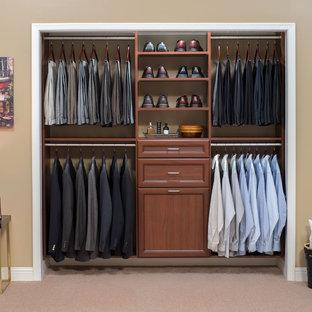 Esempio di un piccolo armadio o armadio a muro per uomo classico con ante in legno scuro, moquette e ante con riquadro incassato