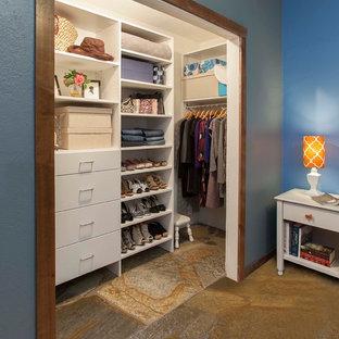 Cette image montre un petit placard dressing traditionnel pour une femme avec un placard à porte plane, des portes de placard blanches et un sol en ardoise.
