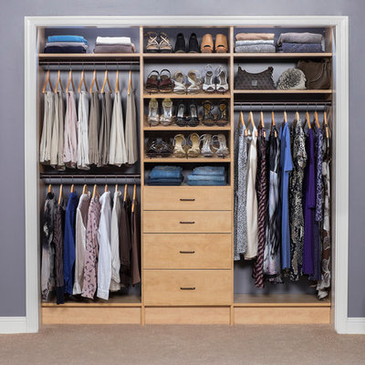 Reach-in closet - small modern women's carpeted reach-in closet idea in New York with flat-panel cabinets and light wood cabinets
