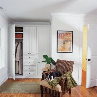 Foto de armario unisex, contemporáneo, de tamaño medio, con armarios con paneles empotrados, puertas de armario blancas y suelo de madera en tonos medios