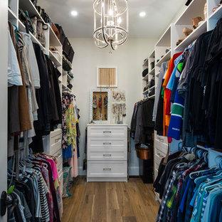 Diseño de armario vestidor unisex, mediterráneo, pequeño, con puertas de armario blancas, suelo de madera en tonos medios y suelo marrón