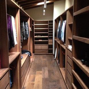 Ejemplo de armario vestidor unisex, contemporáneo, grande, con armarios con paneles lisos, puertas de armario de madera en tonos medios y suelo de madera en tonos medios