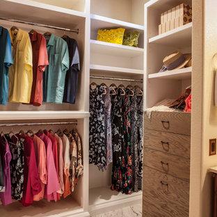 Diseño de vestidor unisex, rural, de tamaño medio, con armarios abiertos, suelo de baldosas de cerámica y puertas de armario con efecto envejecido