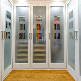 Immagine di una cabina armadio tradizionale con ante di vetro, ante bianche e parquet chiaro