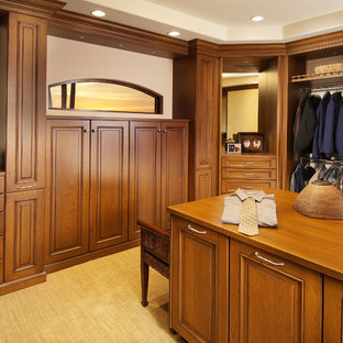 Inspiration for a large transitional men's walk-in wardrobe in Phoenix with raised-panel cabinets, medium wood cabinets and carpet.