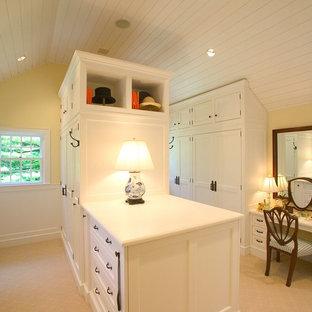 Ejemplo de armario vestidor unisex, campestre, grande, con armarios con paneles empotrados, puertas de armario blancas y moqueta