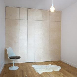 Diseño de vestidor unisex, moderno, grande, con puertas de armario de madera clara y suelo de madera en tonos medios