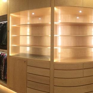 Inredning av ett modernt mycket stort walk-in-closet för könsneutrala, med släta luckor, skåp i ljust trä och ljust trägolv